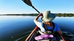 Kobiet płynąca kajakiem po zalewie