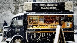 Francuski food truck w śniegu. Czarna furgonetka piekarnia