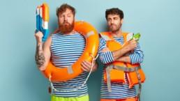 Dwaj animatorzy turystyki w koszulkach w paski. Jeden ma na sobie kapok a drugi koło ratunkowe. Obaj przygotowani są do walki na pistolety wodne.