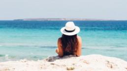 Kobieta w białym kapeluszu leżąca na skałę i patrząca na turkusową morską wodę.